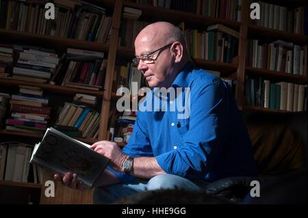 Un homme plus âgé de fumer sa pipe et la lecture d'un livre à la maison. Banque D'Images