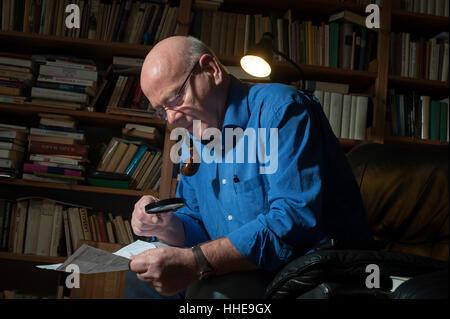 Un homme plus âgé de fumer sa pipe et de la lecture à l'aide d'une loupe à son domicile. Banque D'Images