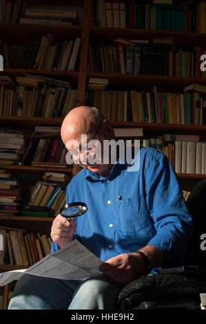 Un homme plus âgé, la lecture à l'aide d'une loupe à son domicile. Banque D'Images