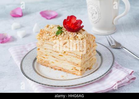 Napoléon, gâteau gâteau en couches avec la crème pâtissière, crème anglaise décoré de rose aux fraises et menthe. Banque D'Images