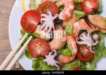 Salade de crevettes, moules, poulpes avec légumes close up sur une plaque avec des baguettes. Vue de dessus Banque D'Images