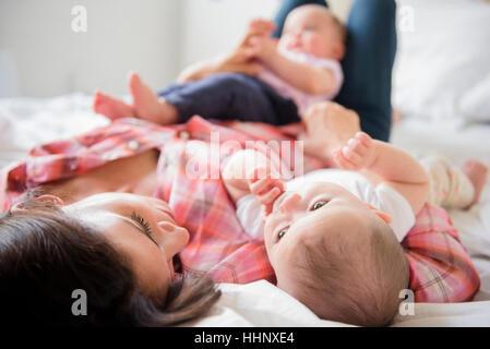 Portrait of woman laying on bed avec lits bébé filles Banque D'Images