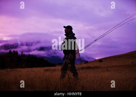 Caucasian man walking et de transporter des cannes à pêche