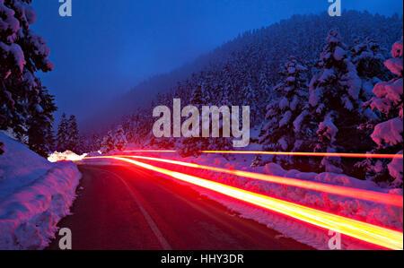 Des sentiers de lumière rouge par une voiture, dans une route dans une région montagneuse de la Grèce, au sein d'une Banque D'Images