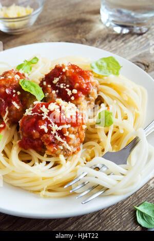 Les pâtes Spaghetti aux Boulettes de viande, sauce tomate, parmesan râpé et de basilic frais - pâtes italiennes Banque D'Images