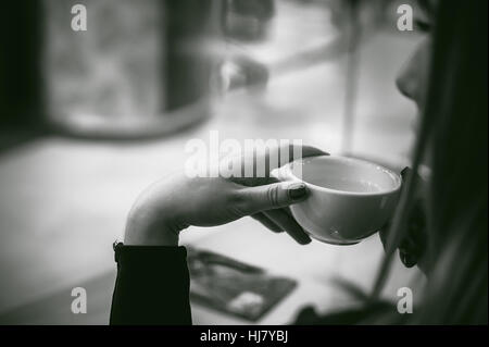 Femme derrière fenêtre dans cafe. Jeune fille en robe noire est assis à table, boissons holding cup Banque D'Images