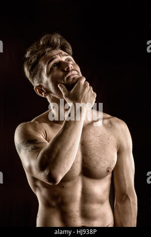 Beau musclé, shirtless man looking up thinking Banque D'Images