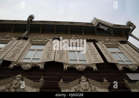 Close up de vieille maison en bois de deux étages en Sibérie. La boiserie de la fenêtre et les volets sont brun Banque D'Images