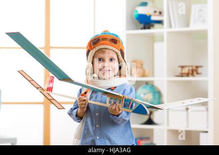 Heureux l'enfant garçon avec modèle de pilote avion rêve de devenir