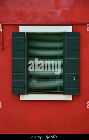 Fenêtre verte dans un mur rouge Banque D'Images