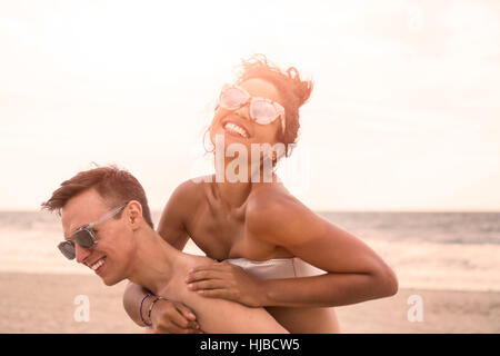 Young man giving piggy back pour petite amie sur Rockaway Beach, New York State, USA Banque D'Images