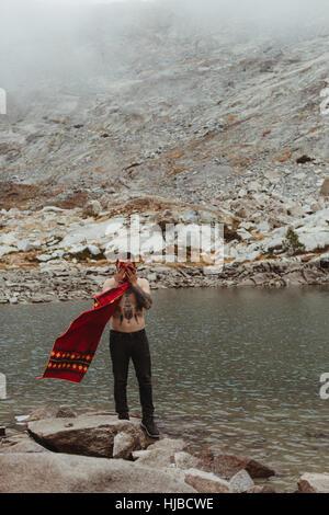 Young male hiker face de séchage avec une serviette au lac, minéral King, Sequoia National Park, Californie, USA Banque D'Images