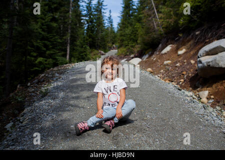 Petite fille assise sur la route de gravier en forêt, Vancouver, British Columbia, Canada Banque D'Images