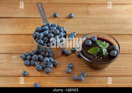 Confiture de bleuets dans un bol en verre avec des bleuets et une tasse à mesurer plein de bleuets sur une surface en bois