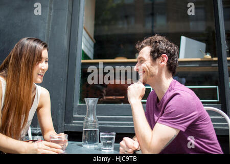 Couple chatting at city sidewalk cafe Banque D'Images