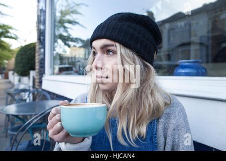 Jeune femme assise café à l'extérieur, de boire une tasse de thé Banque D'Images