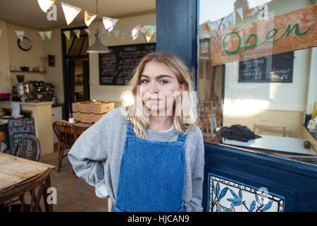 Portrait of young woman standing in doorway de cafe Banque D'Images