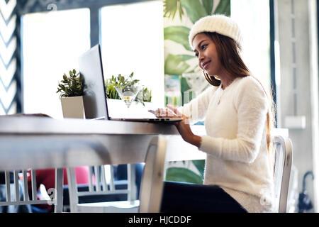 Belle fille en réseau dans un café avec un ordinateur portable Banque D'Images