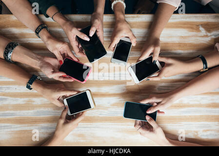 Vue d'en haut les mains à l'aide de cercle téléphone dans un café. Banque D'Images
