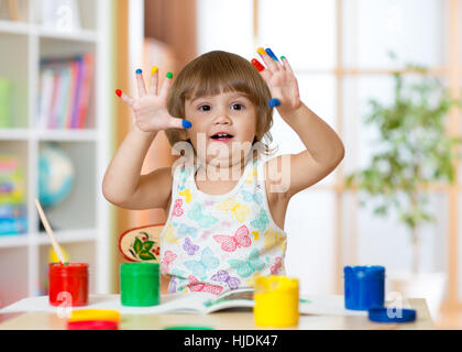 Cute cheerful kid girl montrant ses doigts peints dans des couleurs vives Banque D'Images