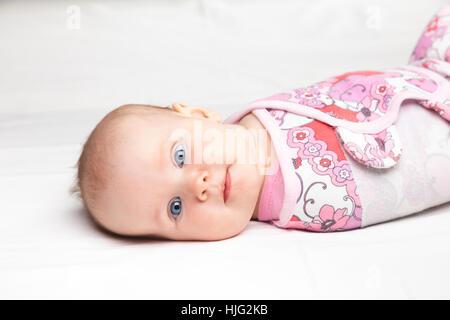 Trois mois bébé fille enveloppée dans un moderne bébé swaddle ailé portant sur un lit. L'emmaillotement est une Banque D'Images
