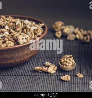 Les cerneaux de noix et les noix entières dans Bol en céramique marron. Aliments biologiques sains concept. La composition Banque D'Images