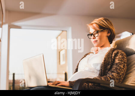 Pregnant woman sitting in armchair using laptop Banque D'Images