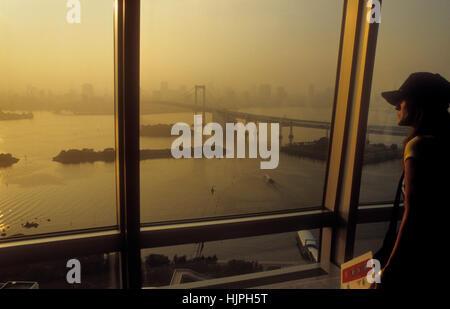 Panorama, paysage urbain, femme, coucher de soleil, baie de Tokyo vu de Fuji TV bâtiment à Odaiba. En Arrière-Plan Banque D'Images