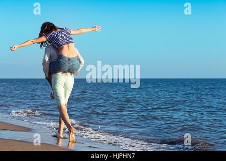 Bel homme piggy back donnant à sa petite amie à la plage Banque D'Images