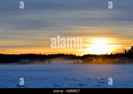 Magnifique coucher de soleil sur la campagne. Champ neigeux sur le premier plan, la brume sur l'arrière-plan. Banque D'Images