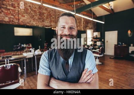 Portrait of happy young coiffure souriant à son barbier. homme de race blanche avec longue barbe debout dans le Banque D'Images