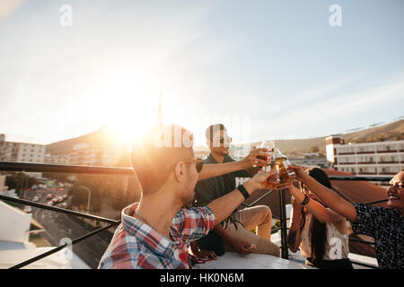 Friends toasting drinks at a party. Young Friends hanging out at rooftop party et profiter de boissons. Banque D'Images