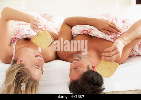 Couple se blottit sous couette Eating Breakfast Banque D'Images