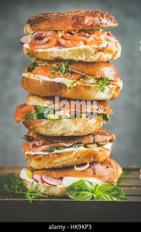 Tas de bagels au saumon, œufs, légumes, câpres, herbes fraîches et crème-fromage, fond de béton gris. Un petit-déjeuner Banque D'Images