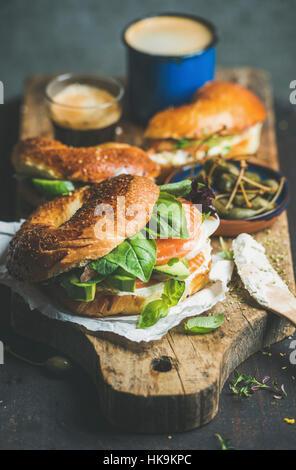 Le petit-déjeuner avec des bagels avec du saumon, avocat, fromage, crème, basilic, câpres, café expresso sur planche Banque D'Images