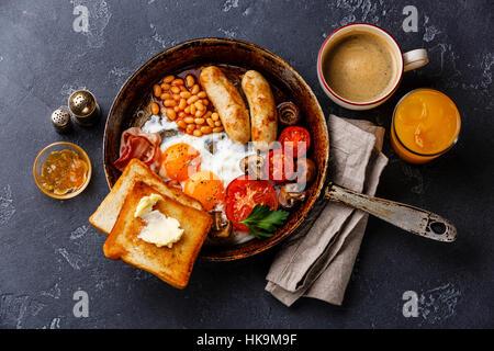 Petit-déjeuner anglais dans la casserole avec les œufs, saucisses, bacon, haricots, des toasts et du café à l'arrière Banque D'Images
