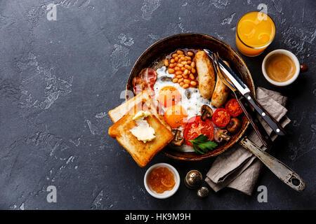 Petit-déjeuner anglais dans la casserole avec les œufs, saucisses, bacon, haricots, toasts et café sur pierre sombre Banque D'Images