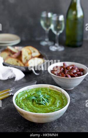 Pesto de basilic ciboulette roquette servi dans un bol en céramique avec crostini, amandes et vin. Photographié Banque D'Images