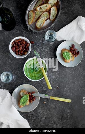 Pesto de basilic ciboulette roquette servi dans un bol en céramique avec crostini, amandes et vin. Banque D'Images
