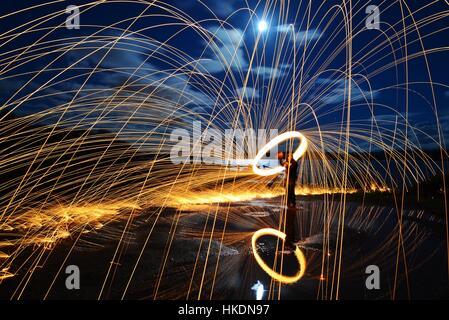 Une longue exposition de la filature de laine d'acier sur un avec étincelles reflétée dans un lac