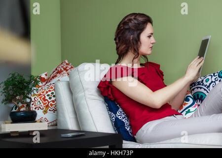 Young caucasian woman using a tablet sur le canapé. Réglage de l'intérieur Banque D'Images