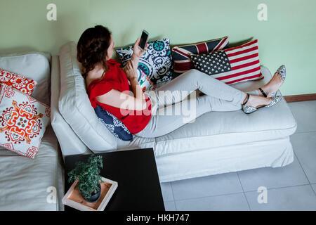 Jeune femme brune en utilisant son smartphone alors qu'elle repose sur le canapé Banque D'Images