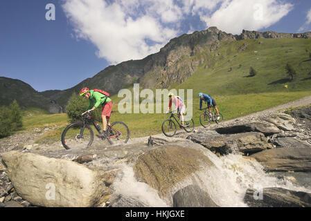 Mountain biker crossing stream on mountain, Zillertal, Tyrol, Autriche Banque D'Images