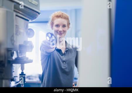 Jeune ingénieur femelle holding pignon dans une installation industrielle, Freiburg im Breisgau, Bade-Wurtemberg, Allemagne
