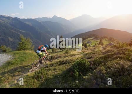 Vélo de montagne équitation sur la pente en paysage alpin pendant le coucher du soleil, Zillertal, Tyrol, Autriche Banque D'Images