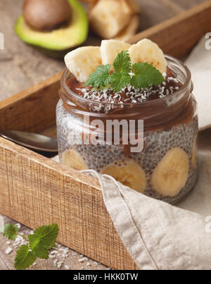 Chia pudding au chocolat smoothie banane avocat dans un bocal en verre sur le vieux fond de bois Banque D'Images