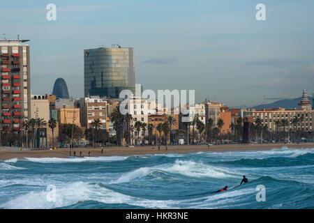 Les surfeurs sur les vagues avec Barcelone à l'arrière. La Catalogne, Espagne.