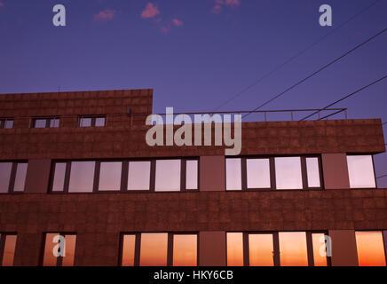 Au crépuscule du bâtiment avec des reflets dans les fenêtres contre ciel violet foncé et rose avec les lignes visibles Banque D'Images