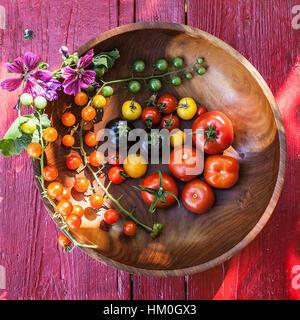 Variété de tomates heirloom dans un bol et sur une surface en bois clair Banque D'Images