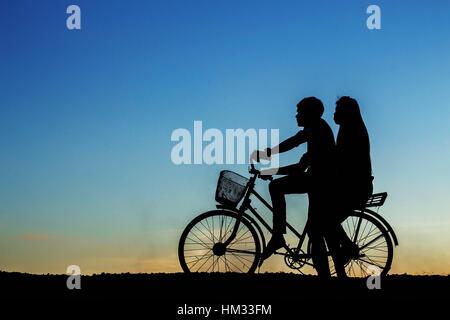 Jeune fille sur un vélo avec les silhouettes. Banque D'Images